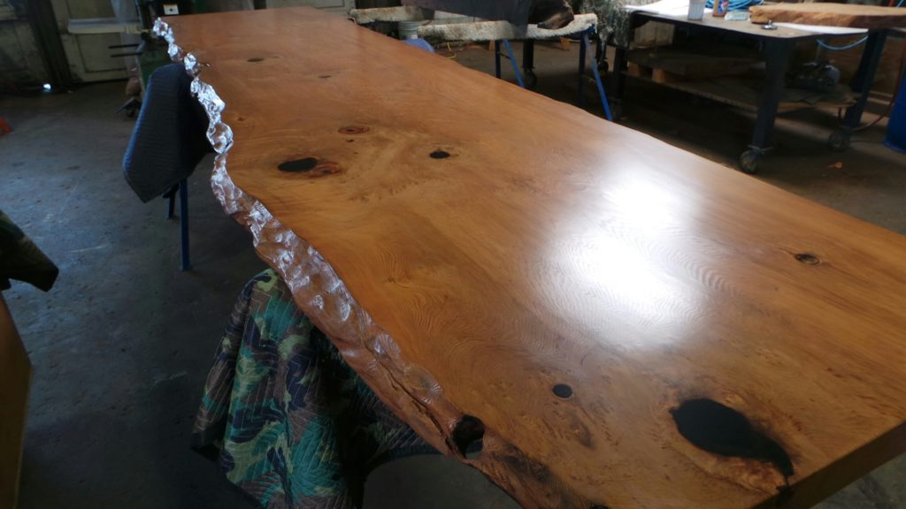 A burl wood table finished in conversion varnish. Conversion varnish is an ideal finish for redwood dining tables and desks.